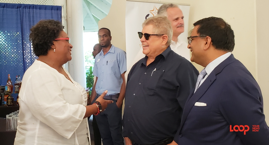 Prime Minister Mia Mottley speaking with Chairman if Sandals Gordon 'Butch' Stewart while Economic Advisor on the Barbados Economic Recovery Team, Professor Avinash Persaud looks on.