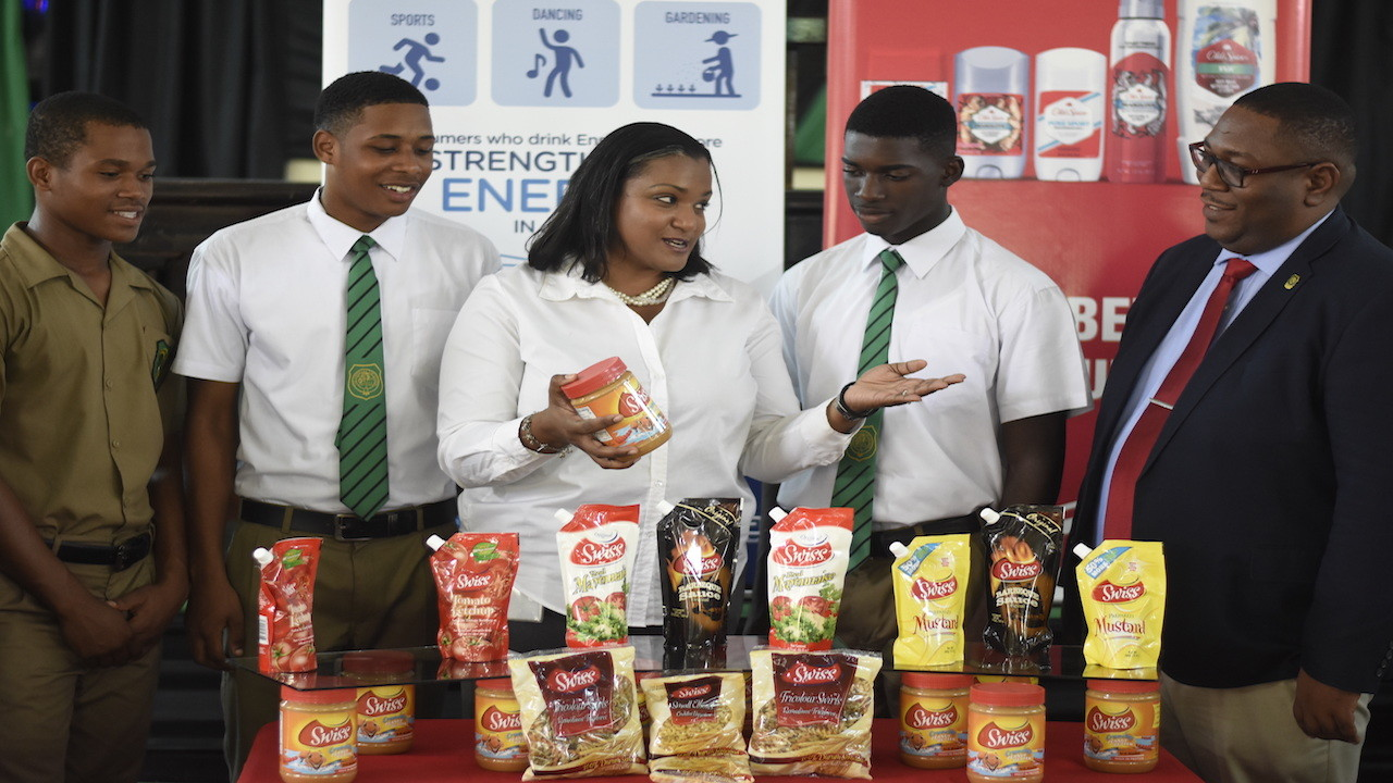 Brand manager at Cari-Med Limited, Nadine Thomas explains the benefits of some of her company's products to Calabar players and acting principal Calvin Rowe. (PHOTOS: Marlon Reid)