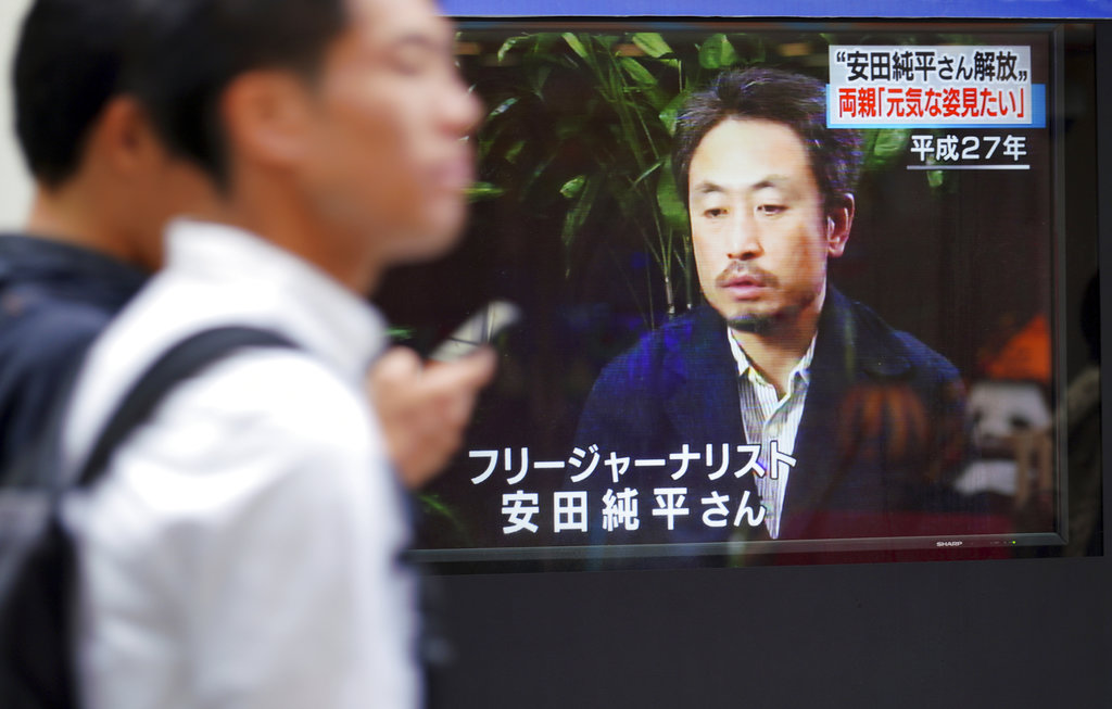 Men walk past a TV screen showing a news program with an image of Japanese freelance journalist Jumpei Yasuda. (AP Photo/Eugene Hoshiko)