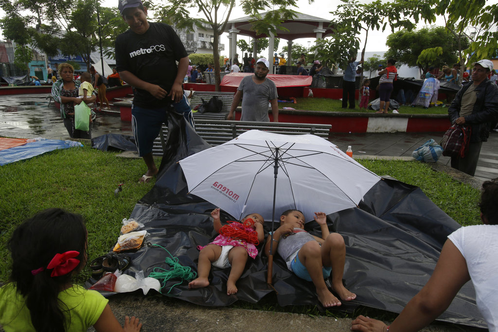 Central American children traveling with a caravan of thousands of migrants rest on a plastic tarp as their parents set up camp in a public park, after arriving to Huixtla, Mexico. (AP Photo/Moises Castillo)