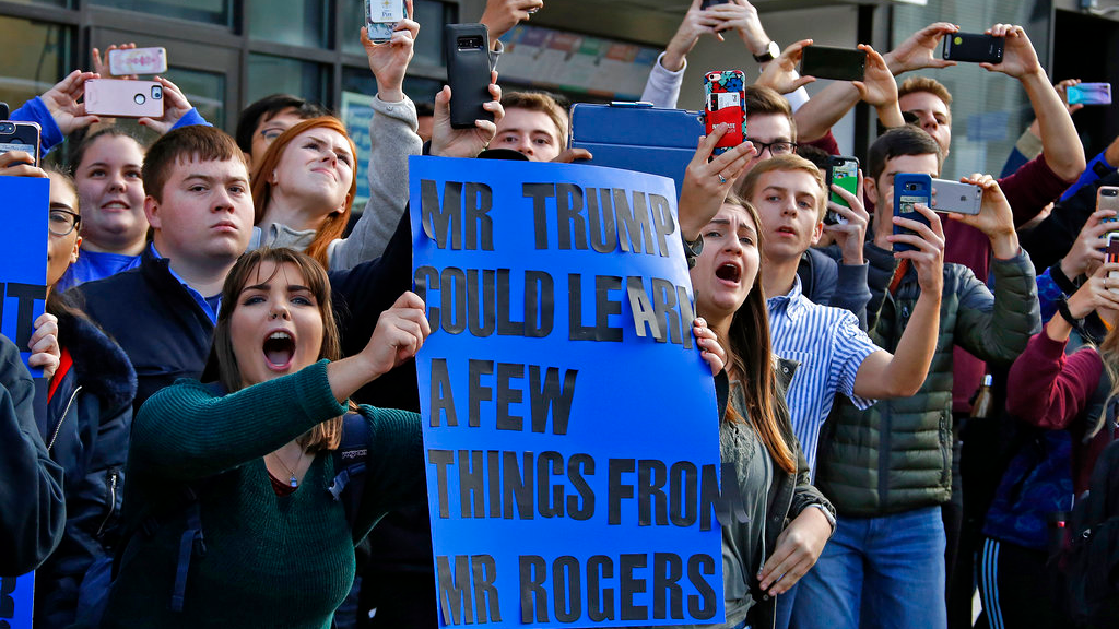 University of Pittsburgh sophomore Lynne Jaworski, from Homer City, Pa., holds a sign and yells as President Donald Trump's motorcade arrives at the University of Pittsburgh's Presbyterian Hospital in Pittsburgh, Tuesday Oct. 30, 2018. (AP Photo/Gene J. Puskar)