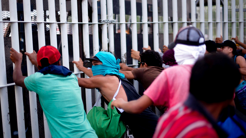 Central American migrants try to force their way through a customs gate at the border bridge connecting Guatemala and Mexico, in Tecun Uman, Sunday, Oct. 28, 2018.  (AP Photo/Santiago Billy)