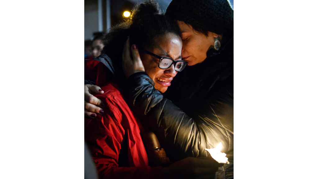 Isabel Kinnane Smith of Allderdice is comforted by Lesley Britton, a math teacher at the school, at a vigil blocks from where an active shooter shot multiple people at Tree of Life Congregation synagogue. (Stephanie Strasburg/Pittsburgh Post-Gazette via AP)