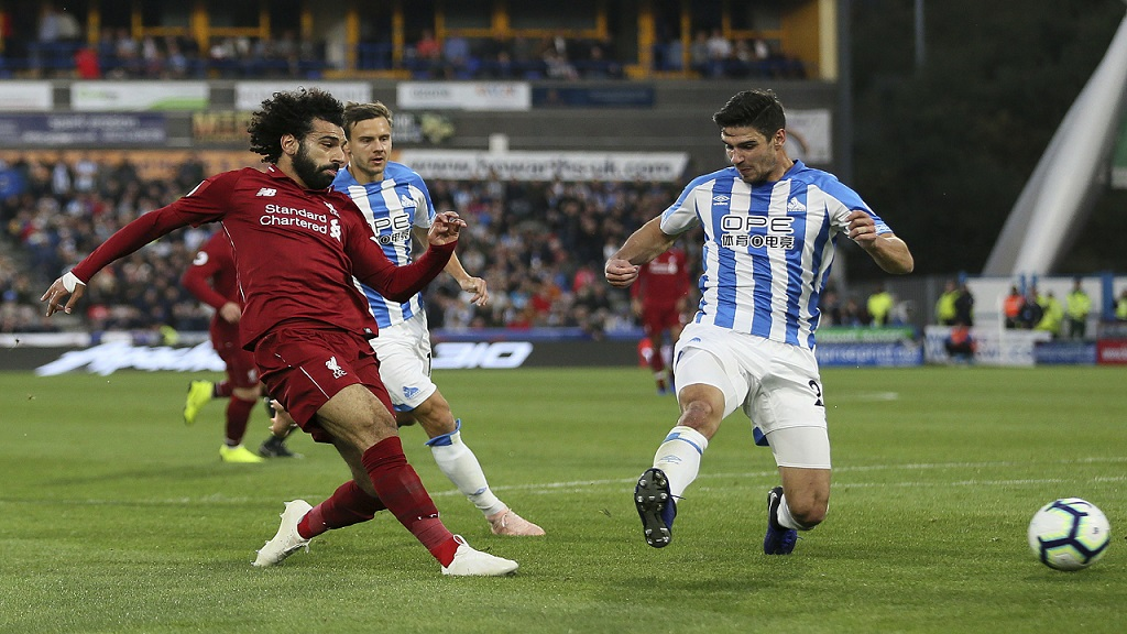 Liverpool's Mohamed Salah (left) scores against Huddersfield Town during their English Premier League football match at the John Smith's Stadium in Huddersfield, England, Saturday, Oct. 20, 2018.