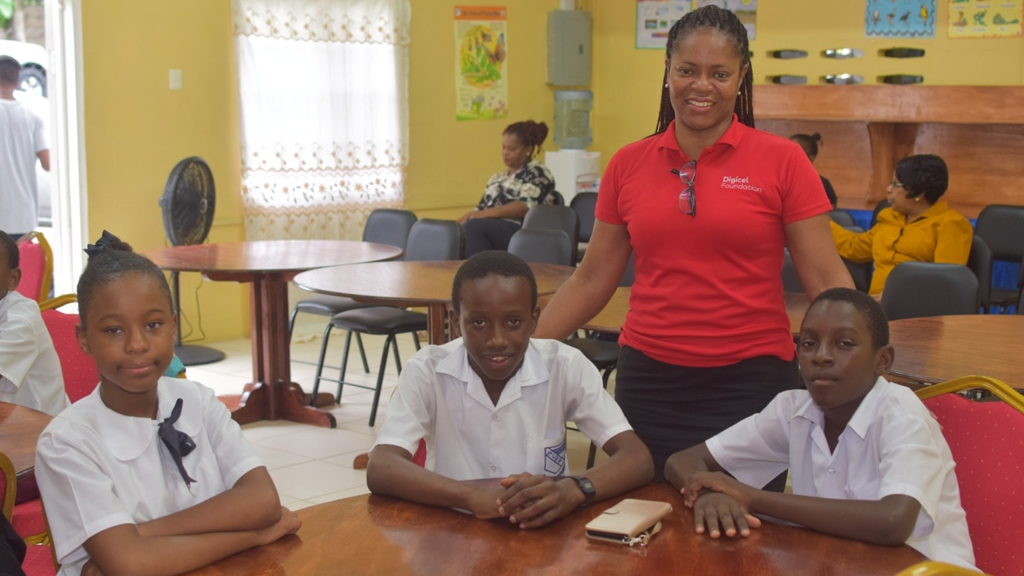 Alicia Hospedales,Digicel Foundation Senior Government Relations and Affairs Executivewith some of the students at the Homework Centre