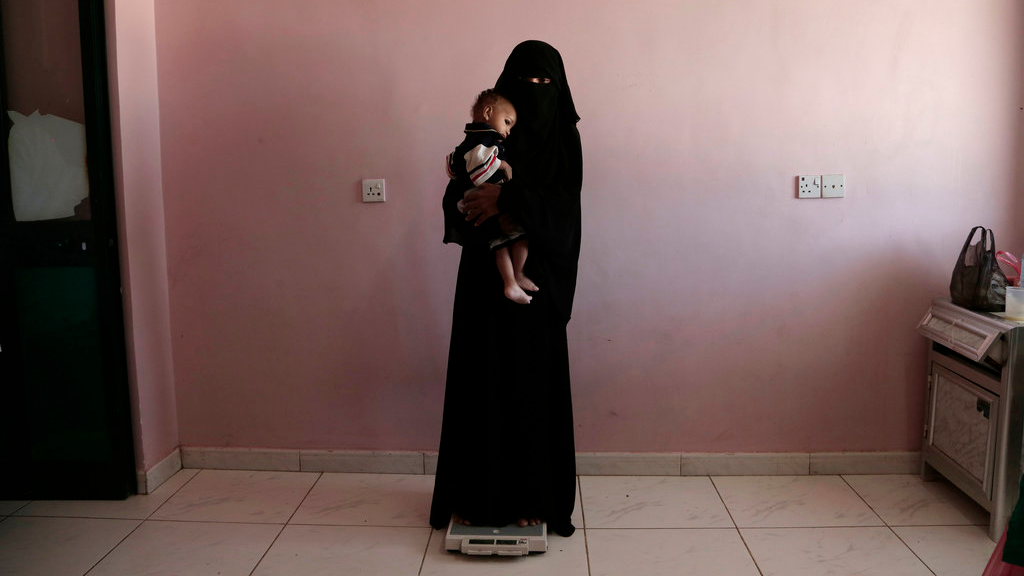 n this Feb. 13, 2018, file photo, Umm Mizrah, a 25-year-old Yemeni woman, holds her son Mizrah on a scale in Al-Sadaqa Hospital in the southern Yemen city of Aden. The woman, who is nearly into the second trimester of her pregnancy, weighed 38 kilograms (84 pounds), severely underweight. Mizrah, who was 17 months old, weighed 5.8 kilograms (12.8 pounds), around half the normal weight for his age. (AP Photo/Nariman El-Mofty, File)