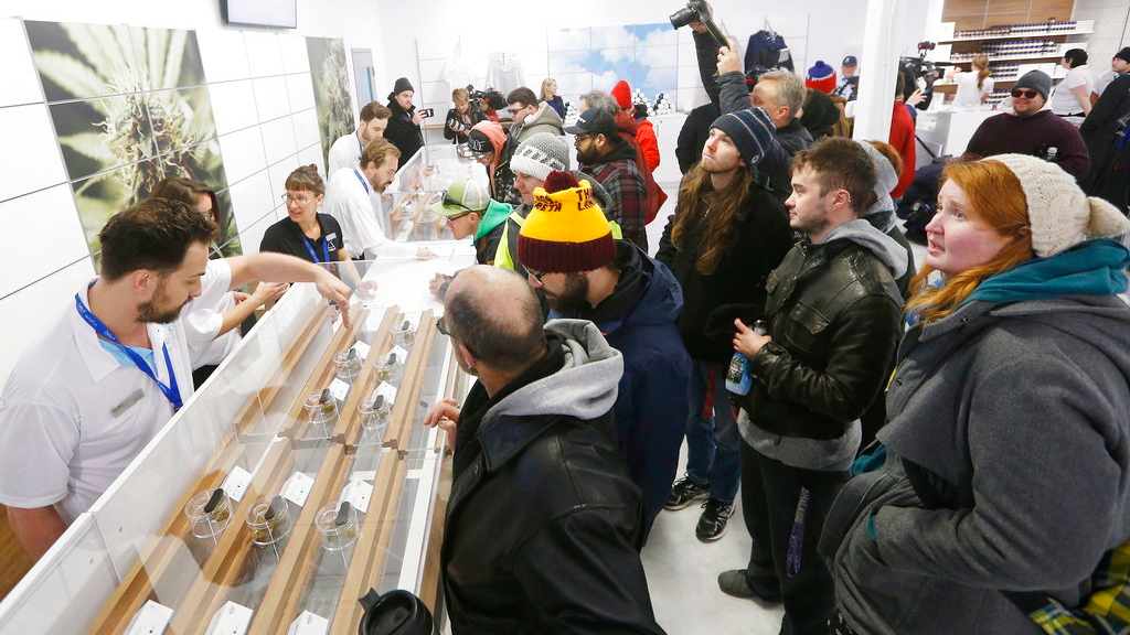 FILE - In this Oct. 17, 2018, file photo, people check out the sample counter at a cannabis store in Winnipeg, Manitoba. Supply shortages have been rampant in the two weeks since Canada became the largest national pot marketplace. (John Woods/The Canadian Press via AP, File)