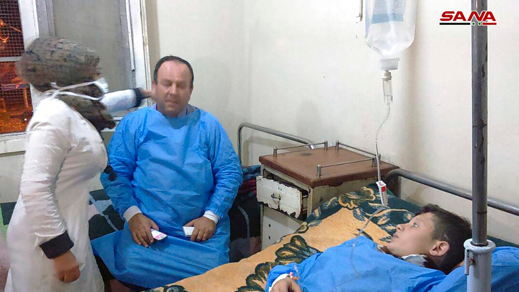 In this photo released by the Syrian official news agency SANA, shows people receiving treatment at a hospital following a suspected chemical attack on his town of al-Khalidiya, in Aleppo, Syria, Saturday, Nov. 24, 2018. At least 41 civilians were being treated following a suspected poison gas attack by Syrian rebel groups on government-held Aleppo city in the country's north, according to Syrian state media. (SANA via AP)