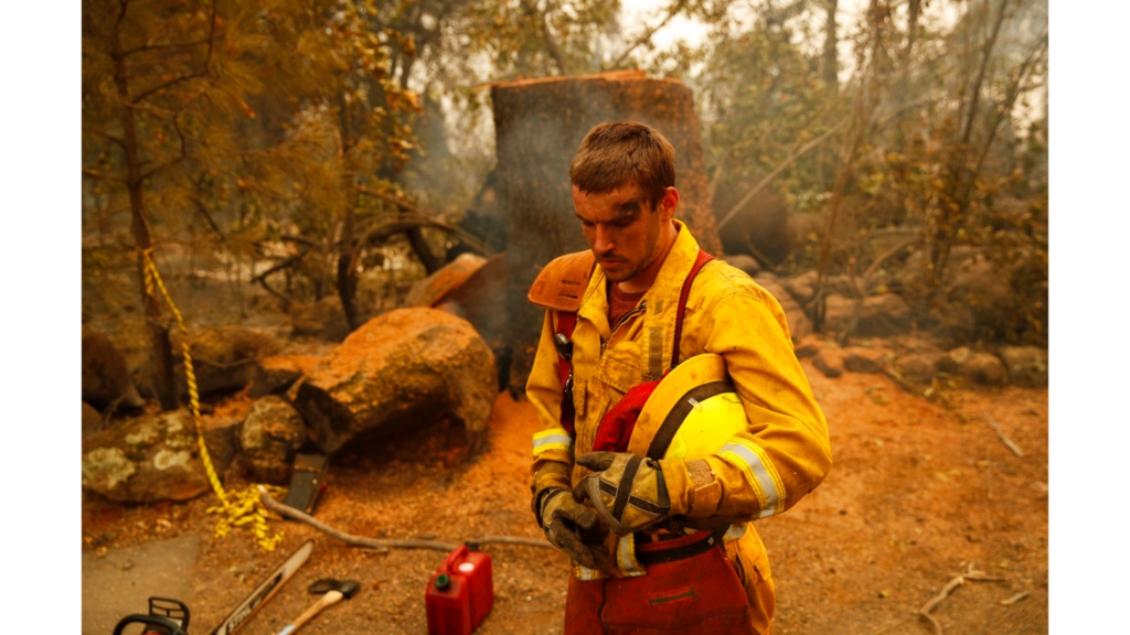 Shawn Slack rests after felling trees burned in the Camp Fire, Monday, Nov. 12, 2018, in Paradise, California. (AP Photo/John Locher)
