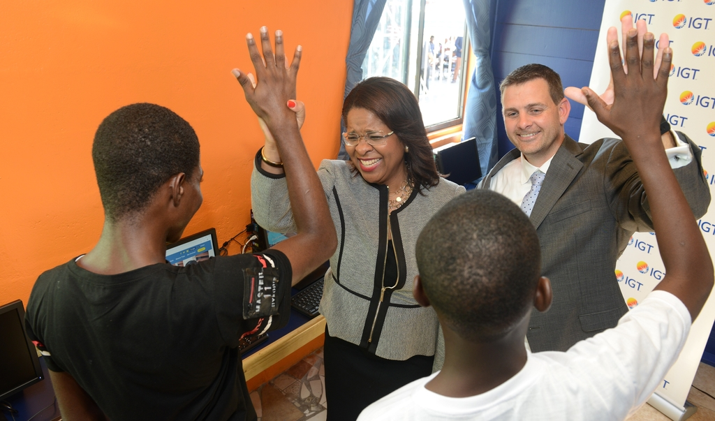 Debbie Green (left), IGT Jamaica General Manager and Brendan Hames, IGT Regional Director, share high fives with residents of Mustard Seed Communities – Matthew 25:40 at the official opening of the IGT After School Advantage Centre. (Photo: Marlon Reid)