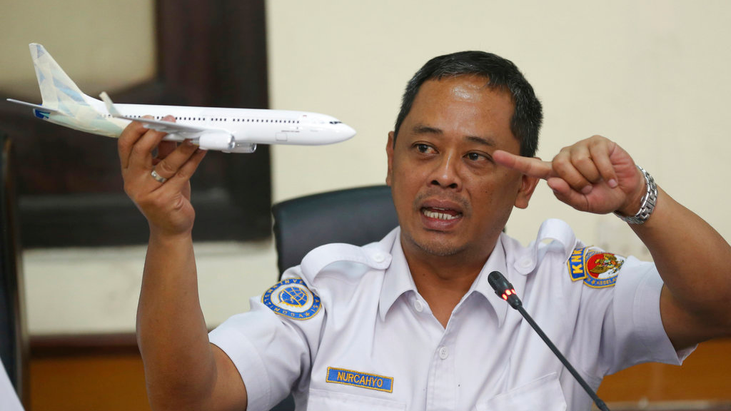 National Transportation Safety Committee investigator Nurcahyo Utomo holds a model of an airplane during a press conference on the committee's preliminary findings on their investigation on the crash of Lion Air flight 610, in Jakarta, Indonesia, Wednesday, Nov. 28, 2018.