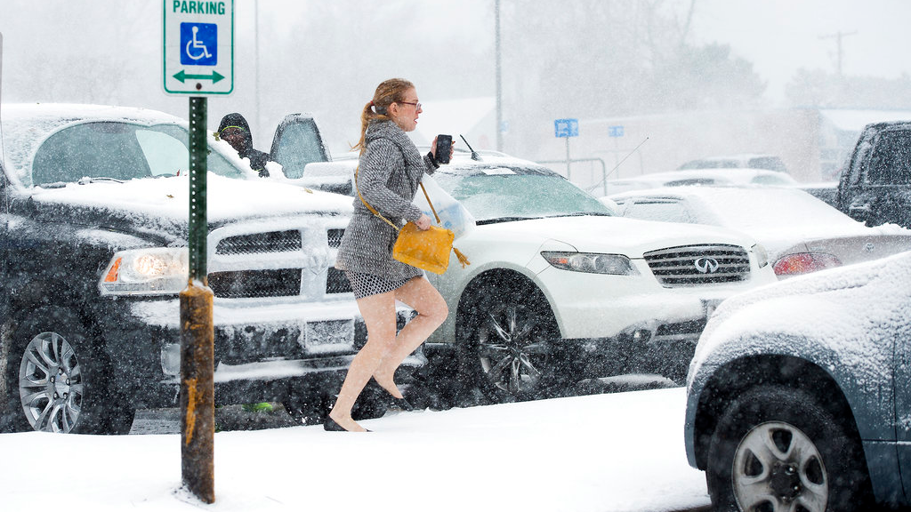 A shopper dashes to her car during a blizzard after shopping Sunday, Nov. 25, 2018, at the Walmart in Roeland Park, Kan. The National Weather Service has issued a blizzard warning for parts of Nebraska, Kansas, Missouri and Iowa. (Tammy Ljungblad/The Kansas City Star via AP)