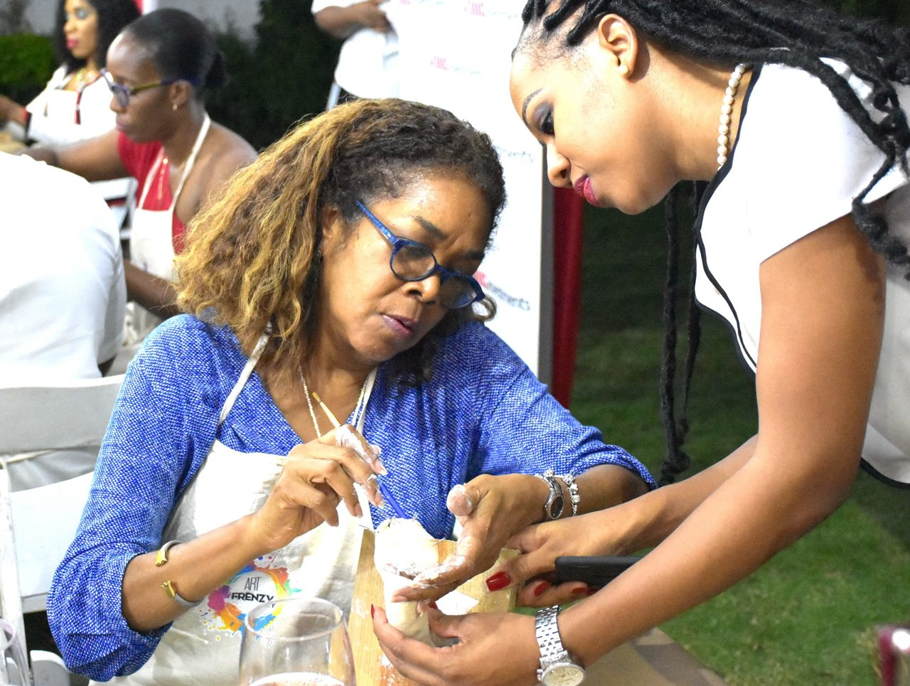 JMMB's Shinelle Simpson (right) demonstrates the true meaning of partnership as she assists international management consultant of J.E. McDonald & Associates to create her masterpiece.