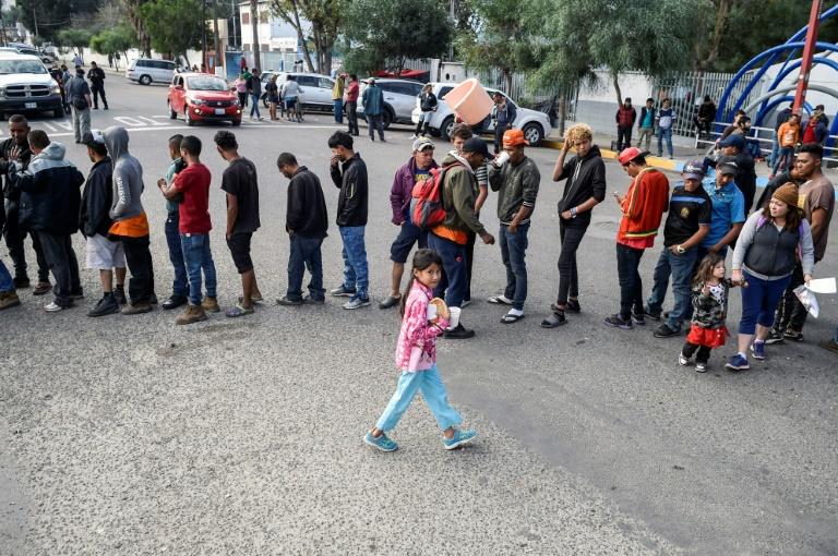 Des migrants d'Amérique centrale essayant de pénéterr aux Etats-Unis font la queue pour une distribution de nourriture à Tijuana au mexique le 15 novembre 2018
