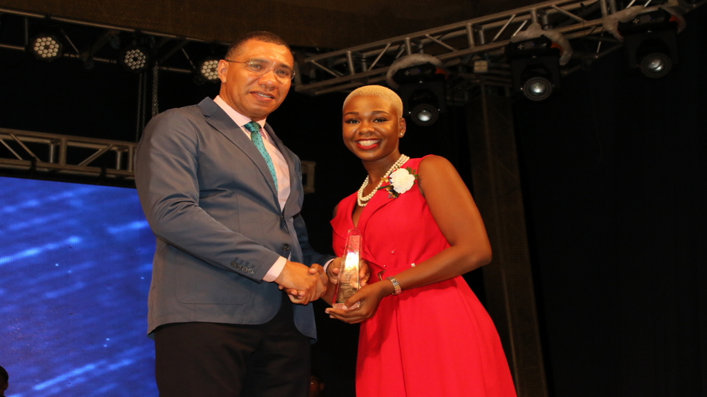 Prime Minister Andrew Holness presents Young People in Business alumna Shawneil Bailey with an award for excellence in entrepreneurship. (Photo: Llewellyn Wynter)