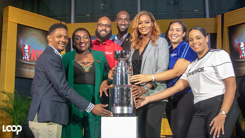ISSA  Champions Cup  sponsors pose with the coveted trophy (from left) Matthew Samuels, product manager, Cetamol; Marsha Lumley, head of marketing, Trade Winds; Andrew Brown, sponsorship manager at Digicel; Andrei Roper, brand manager, KFC; Tanya Lee, vice-president of marketing, SportsMax; Wata's Brand Coordinator Chrys-Ann Gordon; and Amoye Phillpotts-Brown, brand manager of Powerade during the launch at Digicel headquarters in downtown Kingston on Wednesday. (PHOTOS Shawn Barnes).
