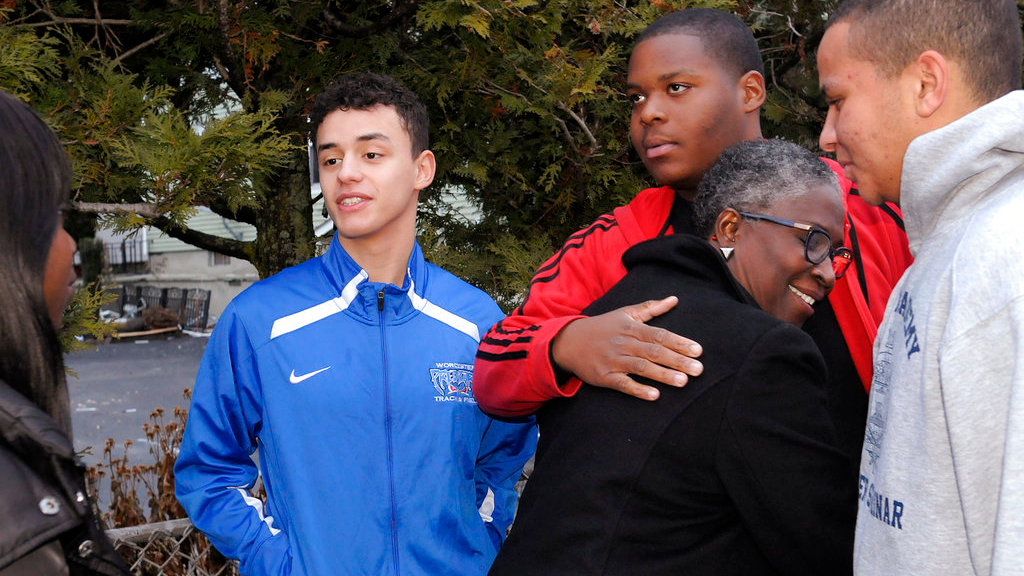 In this Nov. 25, 2018 photo, Edvard Trevant, hugs Raesean Goodney, thanking him and the other boys, Abderrahman Sebbai, left, and Jordan Parker for their quick action during a fire in Worcester, Mass. The three boys and one other member of a Massachusetts high school's JROTC program are being hailed as heroes for rushing into a burning home and rousing the sleeping residents, including several children. (Christine Peterson/Worcester Telegram & Gazette via AP)