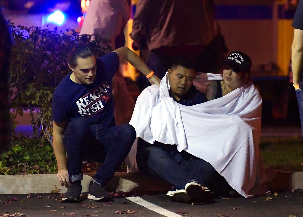 "People comfort each other as they sit near the scene where a gunman opened fire Wednesday inside a country dance bar crowded with hundreds of people on ""college night"". (AP Photo/Mark J. Terrill)"