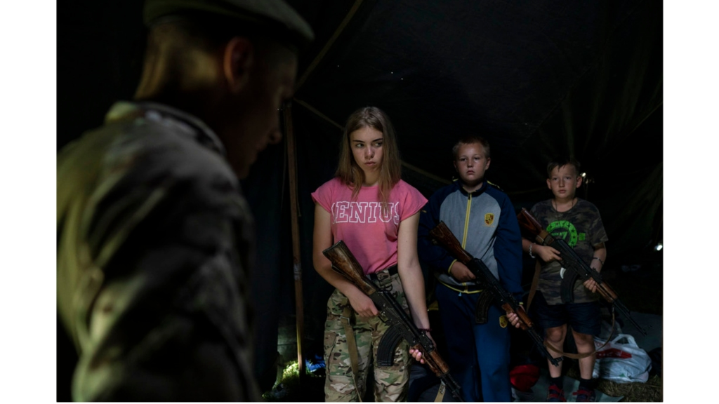 "In this July 28, 2018 photo, participants of the ""Temper of will"" summer camp, organized by the nationalist Svoboda party, hold their AK-47 riffles as they receive instructions during a tactical exercise in a village near Ternopil, Ukraine. Campers as young as 8 years old practice using assault rifles. They are taught to shoot to kill Russians and their sympathizers. (AP Photo/Felipe Dana)"