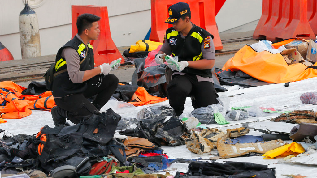 Members of police forensic team inspect personal belongings retrieved from the waters where Lion Air flight JT 610 is believed to have crashed, at Tanjung Priok Port in Jakarta, Indonesia. (AP Photo/Tatan Syuflana)
