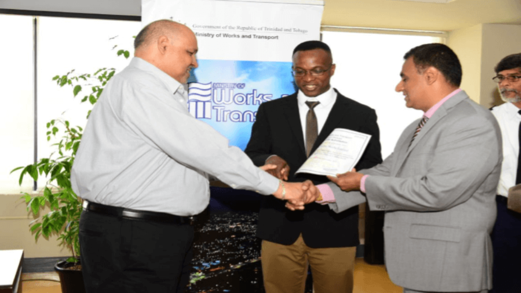 Photo caption: Senator Rohan Sinanan, Minister of Works and Transport presents a certificate of authorisation to Naim Mustapha, Managing Director of Kamus Mufflers Ltd (l), while Mr. Clive Clarke, ICT Director of the Ministry of Works and Transport (centre) looks on. At far right is Mr. Basdeo Gosine, Transport Commissioner (Ag.) Photo courtesy The Ministry of Works and Transport.