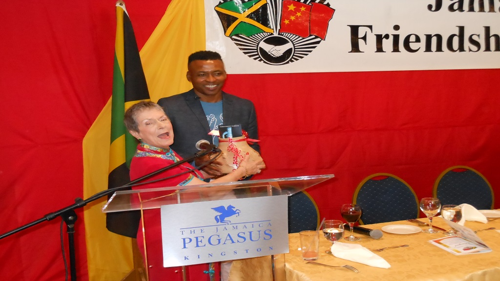 rena Cousins (left) President, Jamaica-China Friendship Association thanks Dr. Kingsley Chin (right) for agreeing to be guest speaker at the JCFA dinner as she prepares to present him with a gift.
