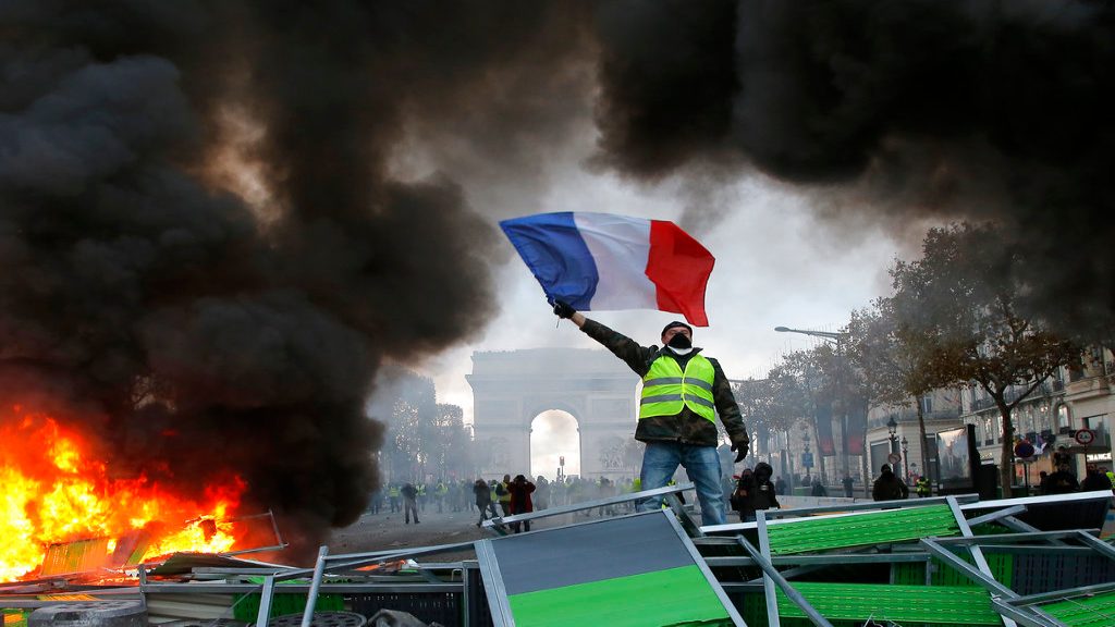 A demonstrator waves the French flag onto a burning barricade on the Champs-Elysees avenue with the Arc de Triomphe in background, during a demonstration against the rising of the fuel taxes, Saturday, Nov. 24, 2018 in Paris. (AP Photo/Michel Euler)