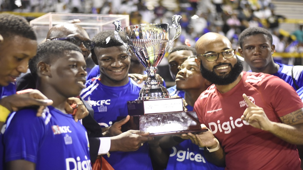 Digicel Regional Sponsorship Manager Andrew Brown (right) presents the Walker Cup to Hydel High following their 2-0 victory over Excelsior High in the final at the Stadium East field on Wednesday, November 14, 2018. (PHOTOS: Marlon Reid).