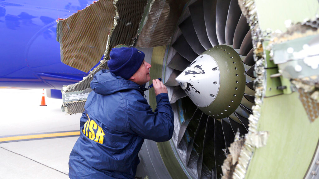 In this April 17, 2018, file photo, a National Transportation Safety Board investigator examines damage to the engine of the Southwest Airlines plane that made an emergency landing at Philadelphia International Airport in Philadelphia.  (NTSB via AP, File)