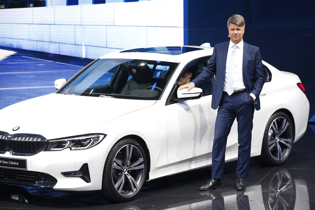 Harald Krüger, the Chairman of the board of management for BMW, stands in front of one of their vehicles.