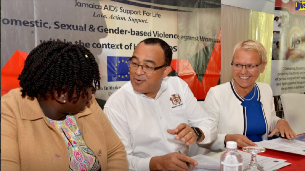 Minister of Health Dr Christopher Tufton (left) speaks with Kandasi Levermore, Executive Director at Jamaica Aids Support. At left is Malgorzata Wasilewska, Head of the European Union Delegation to Jamaica at a public forum on gender-based violence on Wednesday. (Photo: JIS)