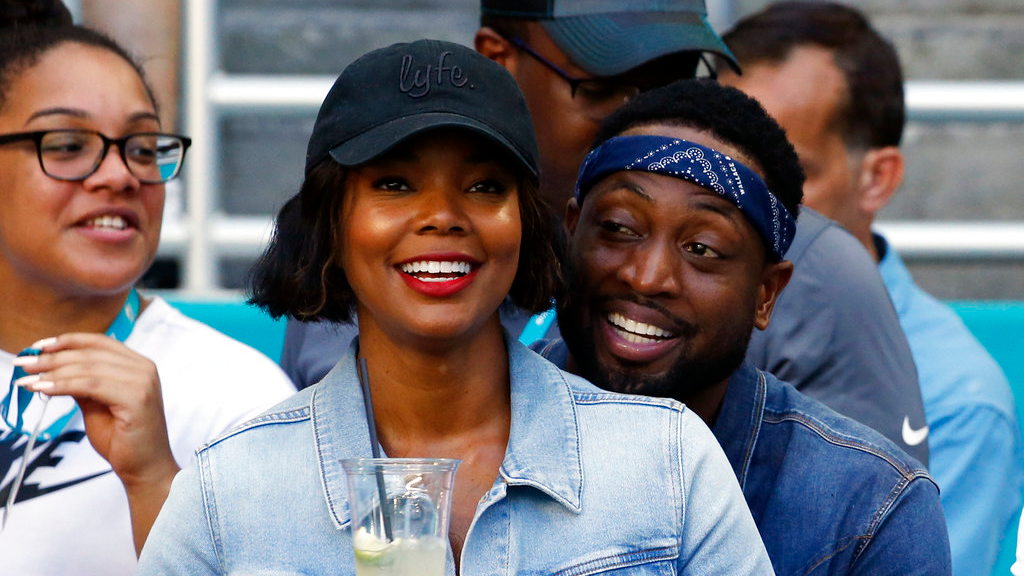 In this Sunday, Oct. 14, 2018 file photo, Miami Heat player Dwyane Wade and his wife Gabrielle Union-Wade acknowledge the cheers from the crowd during the second half of an NFL football game between the Miami Dolphins and the Chicago Bears in Miami Gardens, Fla. (AP Photo/Joel Auerbach, File)