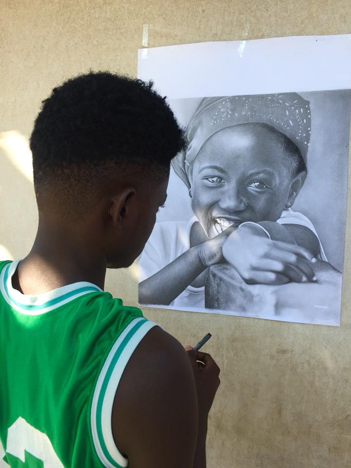 L'artiste et dessinateur Hérold Courtois en train de finaliser le portrait d'un enfant/ Video: Luckenson Jean/ LoopHaiti.