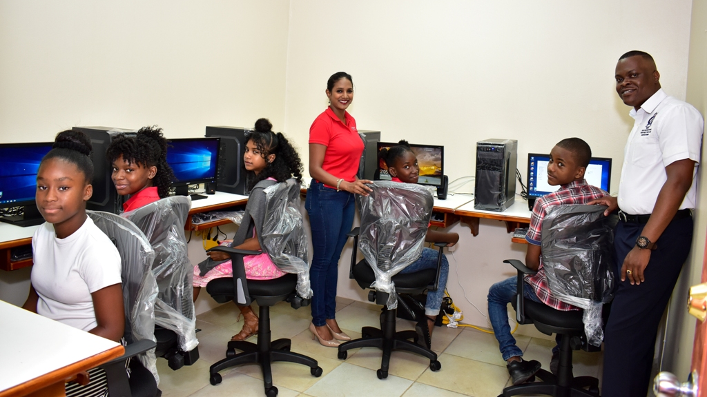 Nia Nanan, Digicel Foundation Project Officer and Officer Kurt Betrand of the Guapo Police Youth Club pose with some of the children from the Guapo community in the new Learning and Resource Centre.