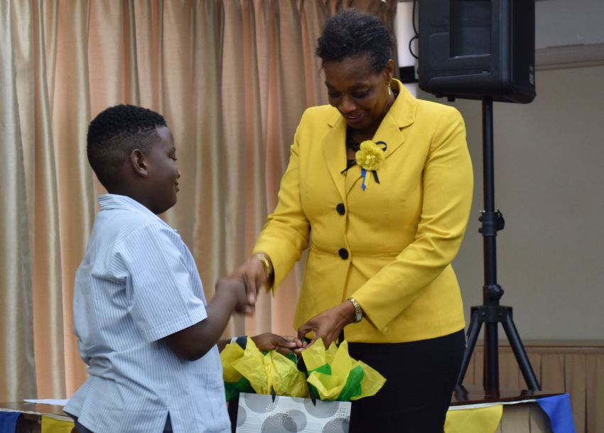 Ten-year-old Giovani Downie of the St. Giles Primary School,  receives his 1st place prize from Acting Postmaster General, Valeta Best. (GP)