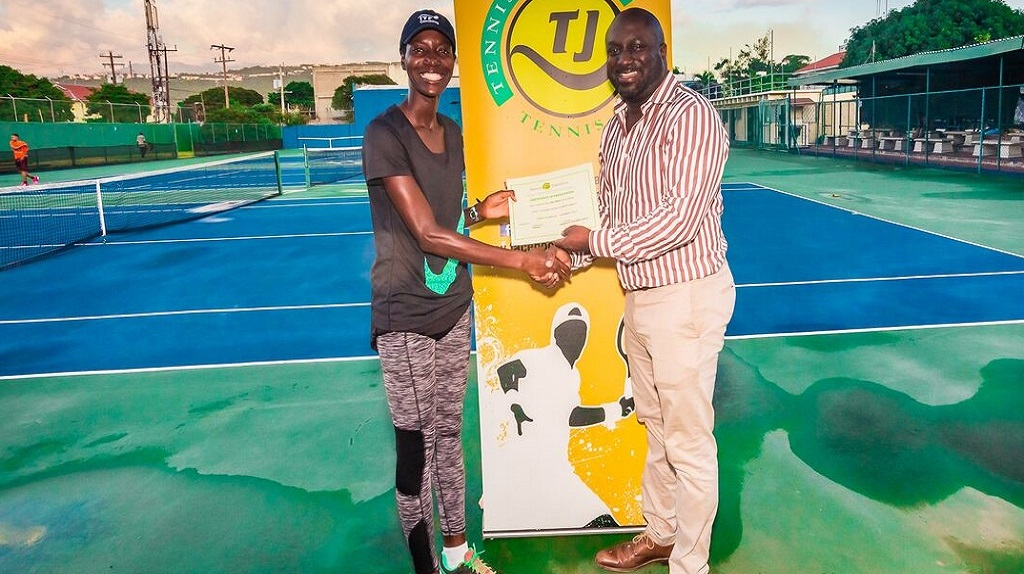 Tinesta Rowe (left) receives her certificate from Tennis Jamaica President Aswad Morgan after successfully competing in the ITF Level One Coaching Certification course at Eric Bell Tennis Centre.
