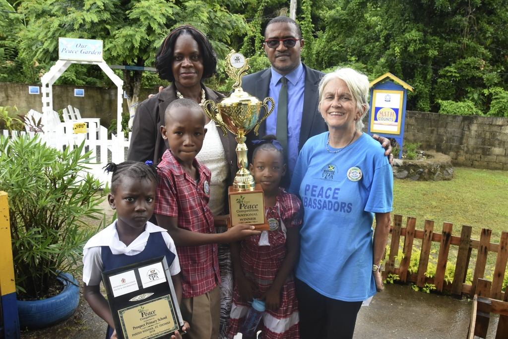 Nesline Lawrence( left in background), principal of Prospect Primary School takes a group photo with her students before the winning Peace Garden in the Trees for Peace Competition. Sharing in the moment are Richard Troupe ( second right in background) , safety and security coordinator at the Ministry of Education,Youth and Information and Dr. Elizabeth Ward, chair of the VPA. The presentation was made to the school last month.