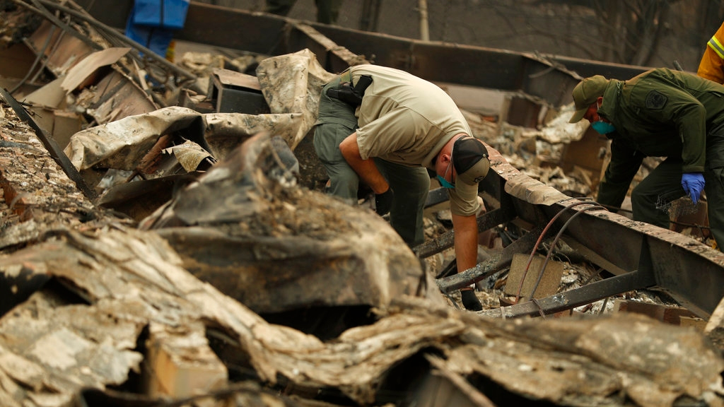 Deputy Coroner Justin Sponhaltz, of the Mariposa County Sheriff's Office, recovers human remains found at a home destroyed by the Camp Fire, Sunday, Nov. 11, 2018, in Paradise, Calif. (AP Photo/John Locher)