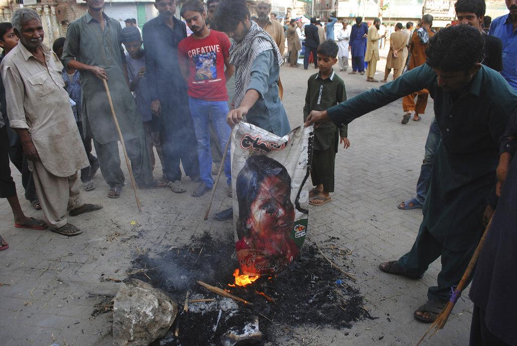 Pakistani protesters burn a poster image of Christian woman Aasia Bibi, in Hyderabad, Pakistan. (AP Photo/Pervez Masih, File)