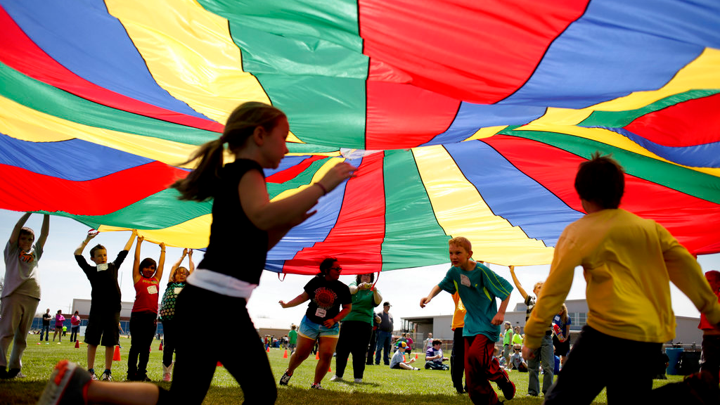 In this Thursday, April 25, 2013 file photo, elementary school third graders run under a rainbow colored tarp during the 15th Annual Kansas Kids Fitness Day, in Hutchinson, Kan.  (Aaron Marineau/The Hutchinson News via AP)