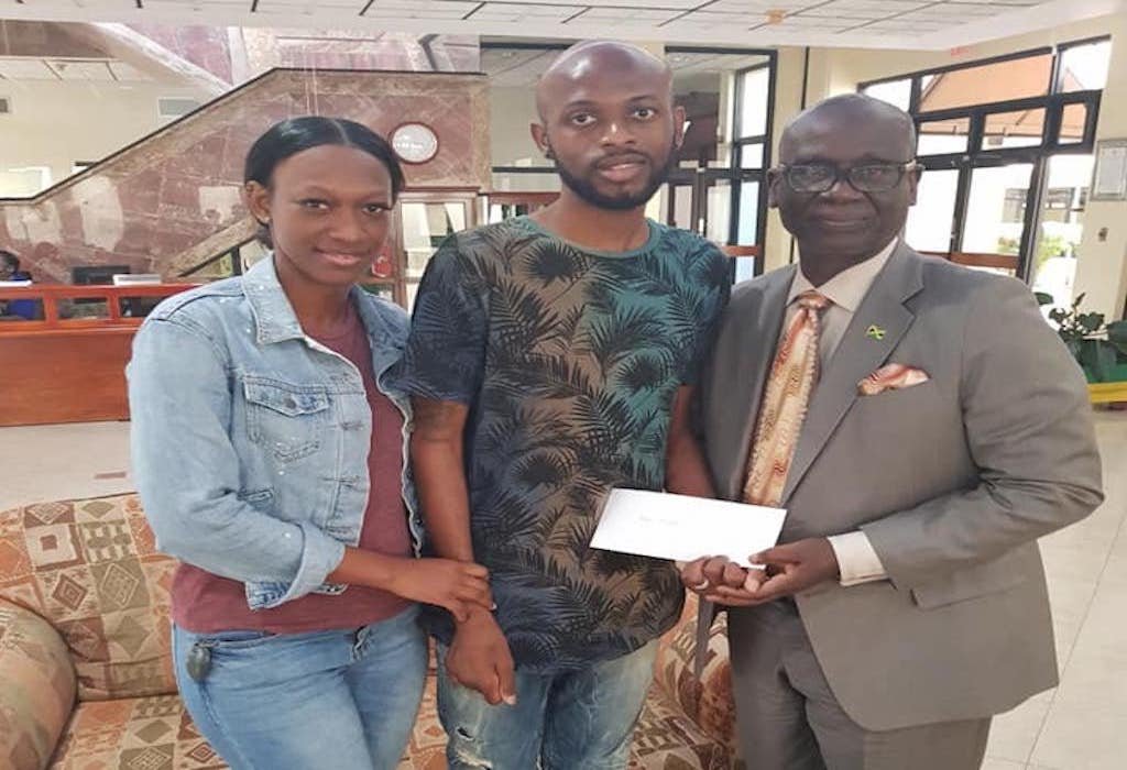 West Kingston MP Desmond McKenzie (right) hands over a cheque to Luton Shelton on Monday. Shelton is joined by his wife, Bobbette.