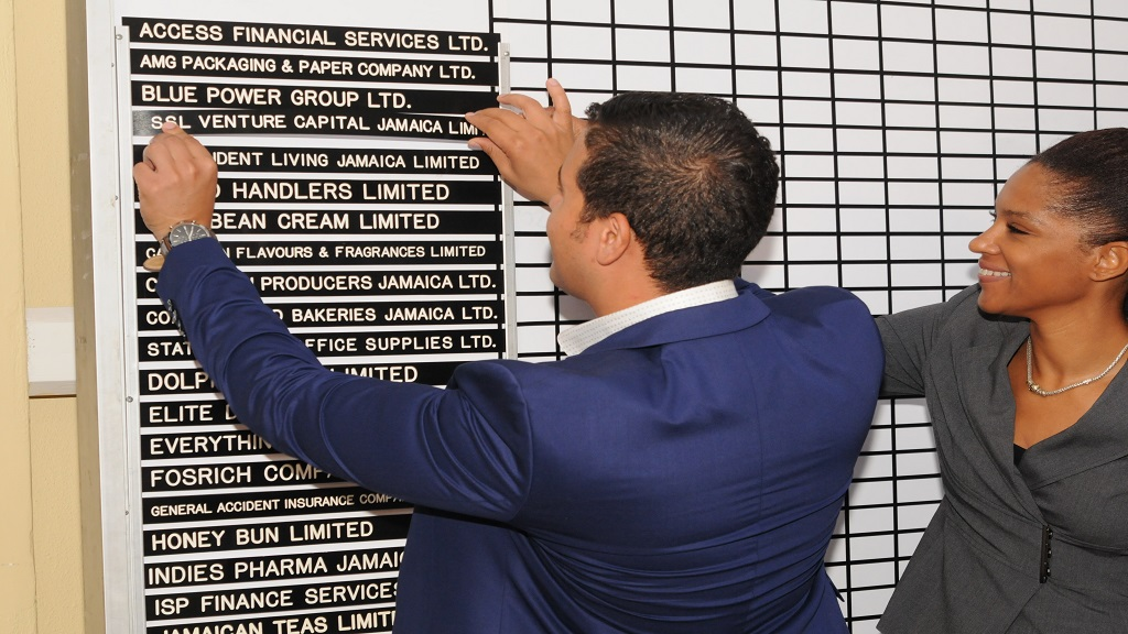 Drew Gray (left), CEO of SSL Ventures places the company's name card on the JSE's trading board. Sharing in the moment is Lamar Harris, CEO of Stocks and Securities Limited. (Filt photo).