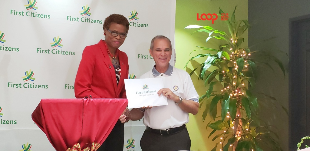 First Citizens Bank, CEO, Carole Eleuthere-Jn Marie presents their sponsorship donation to President-Elect Peter Williams for Carols by Candlelight 2018.