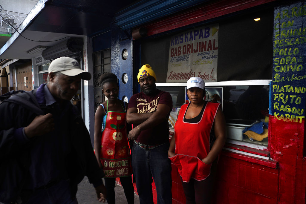 Haitian immigrant Wilthene Pierre poses for a photo with two of his cooks Emily, left, and Violette Novembre, in front of the Kriskapab Baborijinal Haitian restaurant in Tijuana, Mexico, Thursday, Nov. 22, 2018.  (AP Photo/Ramon Espinosa)
