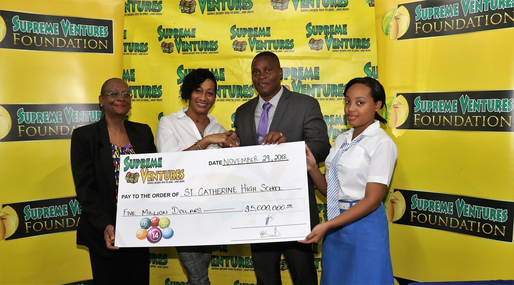 Supreme Ventures Chief Marketing Officer, Heather Goldson [2nd left] presents a symbolic cheque to Principal of the St. Catherine High School, Marlon Campbell during the handover ceremony at the school on Thursday, November 29. Sharing in the moment are Sharon Dale, Chairman of the Board of Governors and a student.