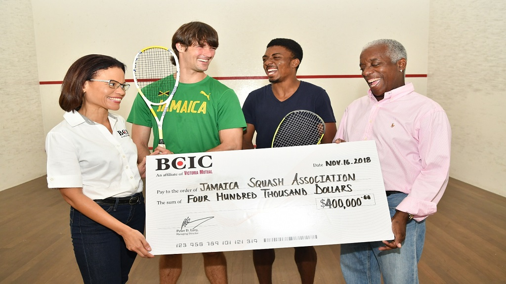 BCIC's Marketing Manager, Simone Foote (far left) hands over her company's sponsorship contribution of $400,000 for the staging of the 2018 All Jamaica Senior Squash Championships to (from left) senior national team players, Tahjia Lumley and Bruce Burrowes and Jamaica Squash Association Executive, Noel McKrieth.
