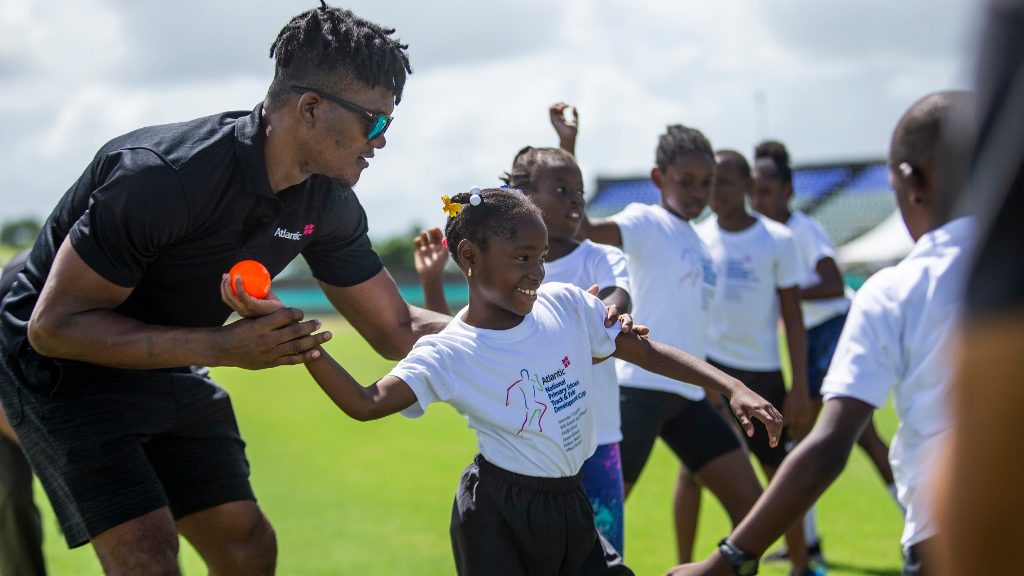 Trinidad and Tobago Olympic Gold Medalist Keshorn Walcott helps a youngster perfect her throwing technique