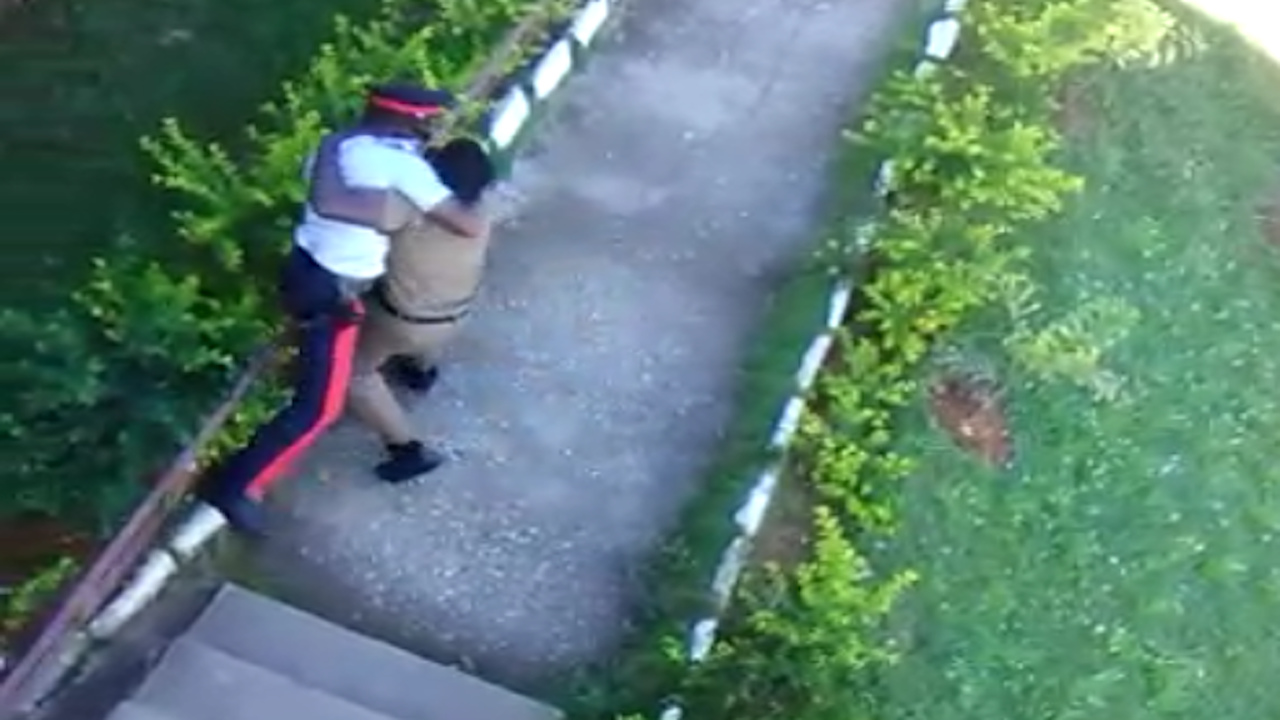 Screenshot of a video showing a policeman and a student wrestling on the Kellits High School compound in Clarendon.