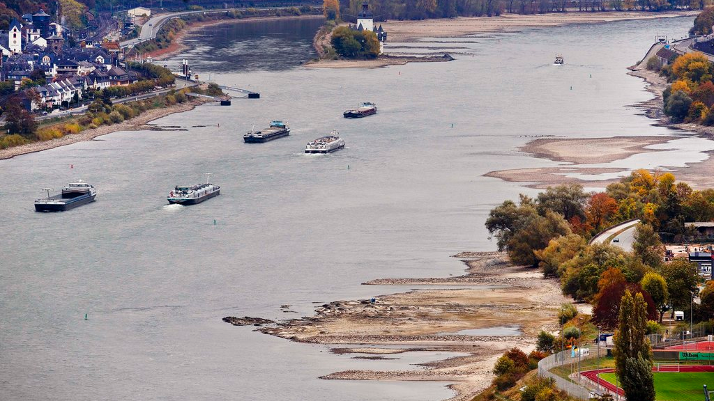 In this Oct. 2018 file photo cargo ships pass sandbanks in the river Rhine near Oberwesel, Germany, during historically low water levels. A hot, dry summer has left German waterways at record low levels, causing chaos for the inland shipping industry, environmental damage and billions of euros of losses _ a scenario that experts warn could portend things to come as global temperatures rise. (AP Photo/Michael Probst)