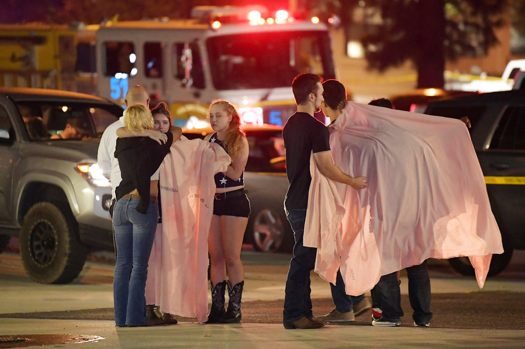 "People comfort each other as they stand near the scene where a gunman opened fire Wednesday inside a country dance bar crowded with hundreds of people on ""college night"". (AP Photo/Mark J. Terrill)"